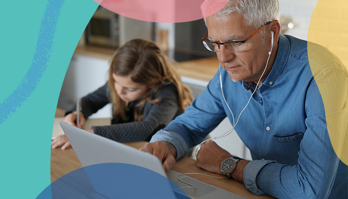An older man wearing ear buds and working on a laptop at a table next to a little girl writing with a pencil.