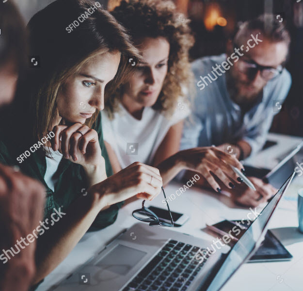 4 people gathered together to look at one woman's laptop.