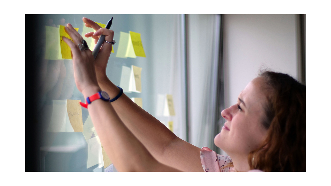 A woman with a Sharpie in her hand, putting yellow post-its on a window.