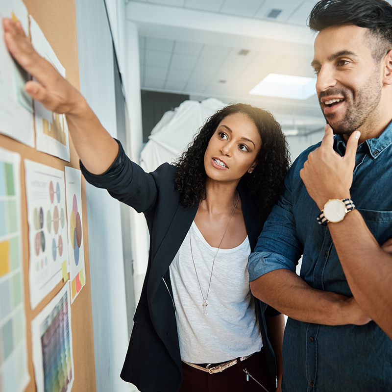 2 people standing and looking at a board with lots of charts, reports and graphs on it. The woman is pointing to one of them.