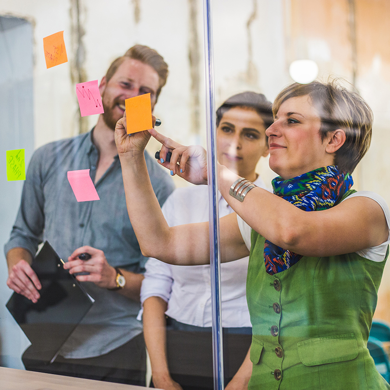 3 people looking at post it notes on a window. One woman writes on one of the post its.